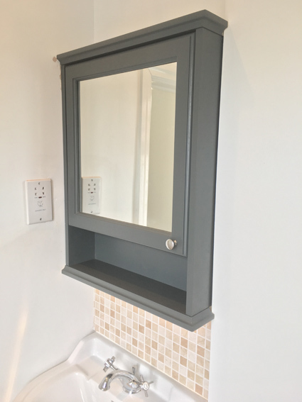 Dark blue bathroom cabinet cut to fit in alcove