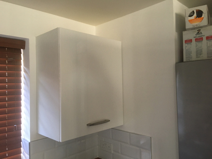 a white gloss kitchen wall cabinet fitted on a wall in a timber framed house