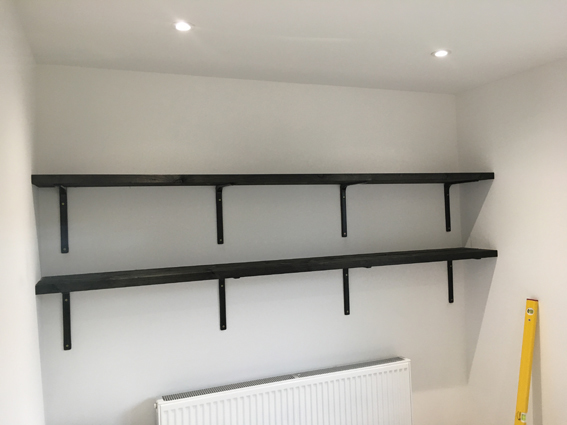 Chunky timber shelves, stained black, with black metal brackets fitted in home office