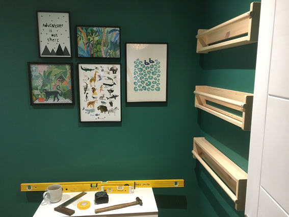 IKEA Flisat wall storage, picture shelves and photo gallery hung on a green painted wall with tools