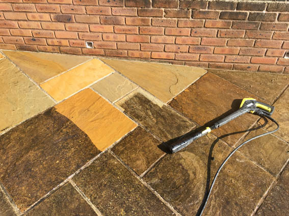 Indian sandstone paving and brick wall being cleaned with a Karcher K7 pressure washer