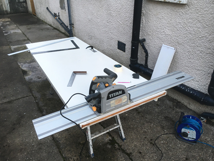 Titan track saw, plunge saw cutting a timber door down to size